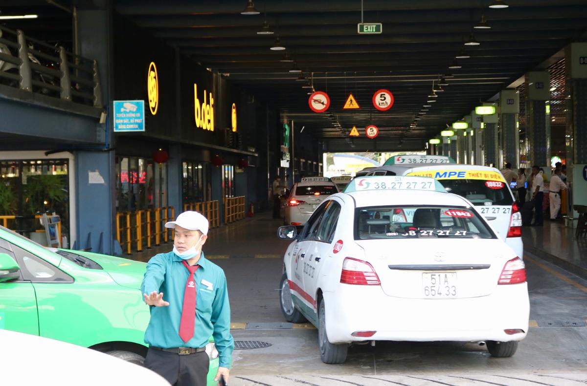Nhân viên điều phối taxi vào làn D sân bay Tân Sơn Nhất, chiều 17/11. Ảnh: Gia Minh.