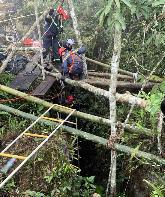 Thiếu tá Thành đeo ròng rọc điện, được các đồng đội hỗ trợ xuống hang. Ảnh: PC07 cung cấp.