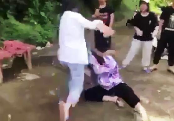 Nữ sinh THCS Nguyễn Văn Trỗi mặc đồng phục thúc gối, đấm đá vào mặt bạn. Ảnh chụp từ clip.