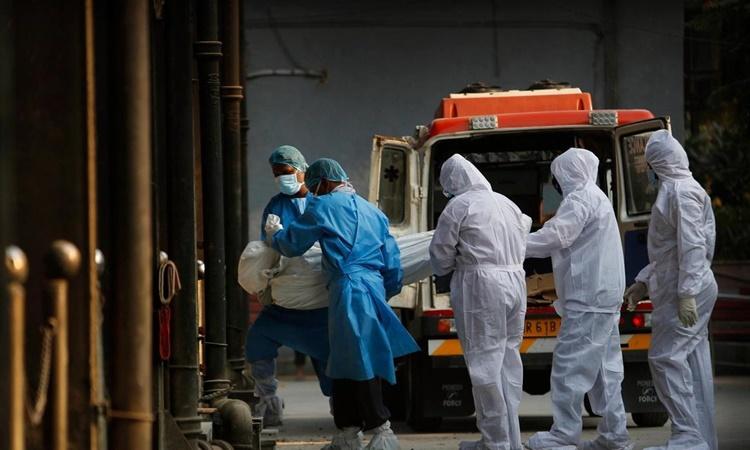 Nhân viên y tế và người thân di chuyển thi thể của một bệnh nhân Covid-19 tại thủ đô New Delhi, Ấn Độ. Ảnh: AP.