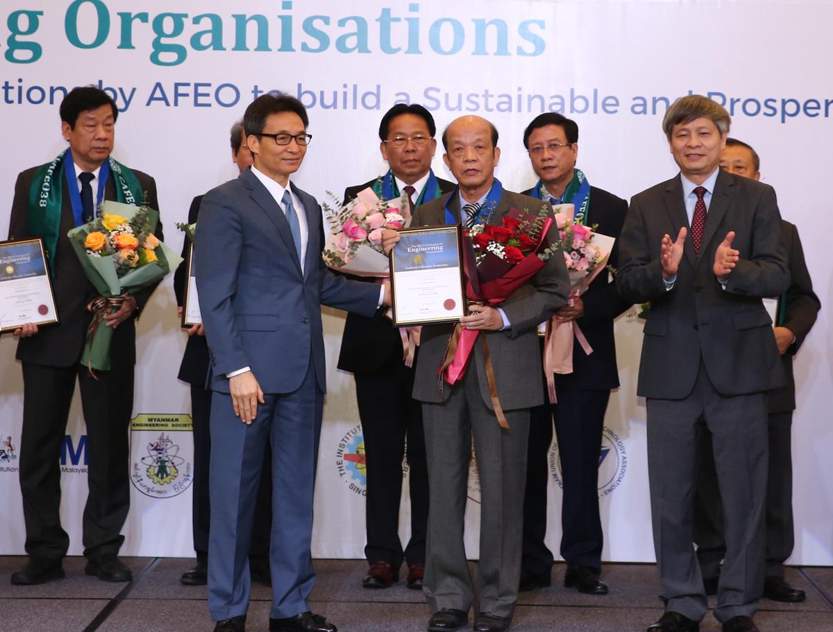 Phó Thủ tướng Vũ Đức Đam (bìa trái), Thứ trưởng Bộ Khoa học và Công nghệ Phạm Công Tạc trao chứng nhận của Liên đoàn Kỹ sư ASEAN cho các cá nhân có nhiều cống hiến. Ảnh: Đình Nam.