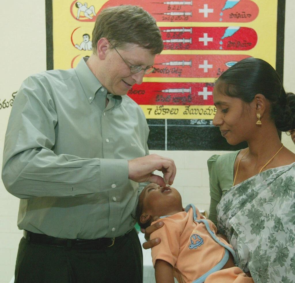 Bill Gates cho một em bé uống vaccine phòng bại liệt năm 2002 tại Ấn Độ. Ảnh: Jeff Christensen
