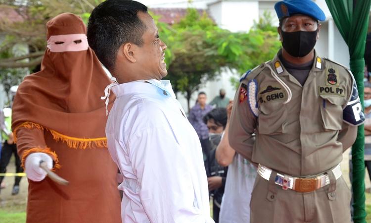 Tên tội phạm cưỡng hiếp trẻ em bị phạt roi ở tỉnh Aceh, Indonesia, hôm 26/11. Ảnh: AFP.