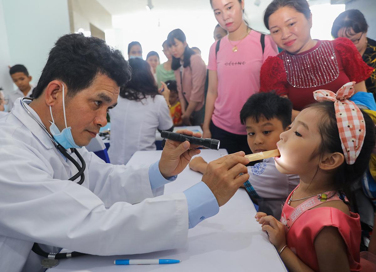 Bác sĩ Nguyễn Vũ Linh, Trưởng ban đào tạo và truyền thông dinh dưỡng, Trung tâm dinh dưỡng Vinamilk thăm khám cho các em trong trong ngày hội hôm 24/11. Ảnh: Quỳnh Trần.