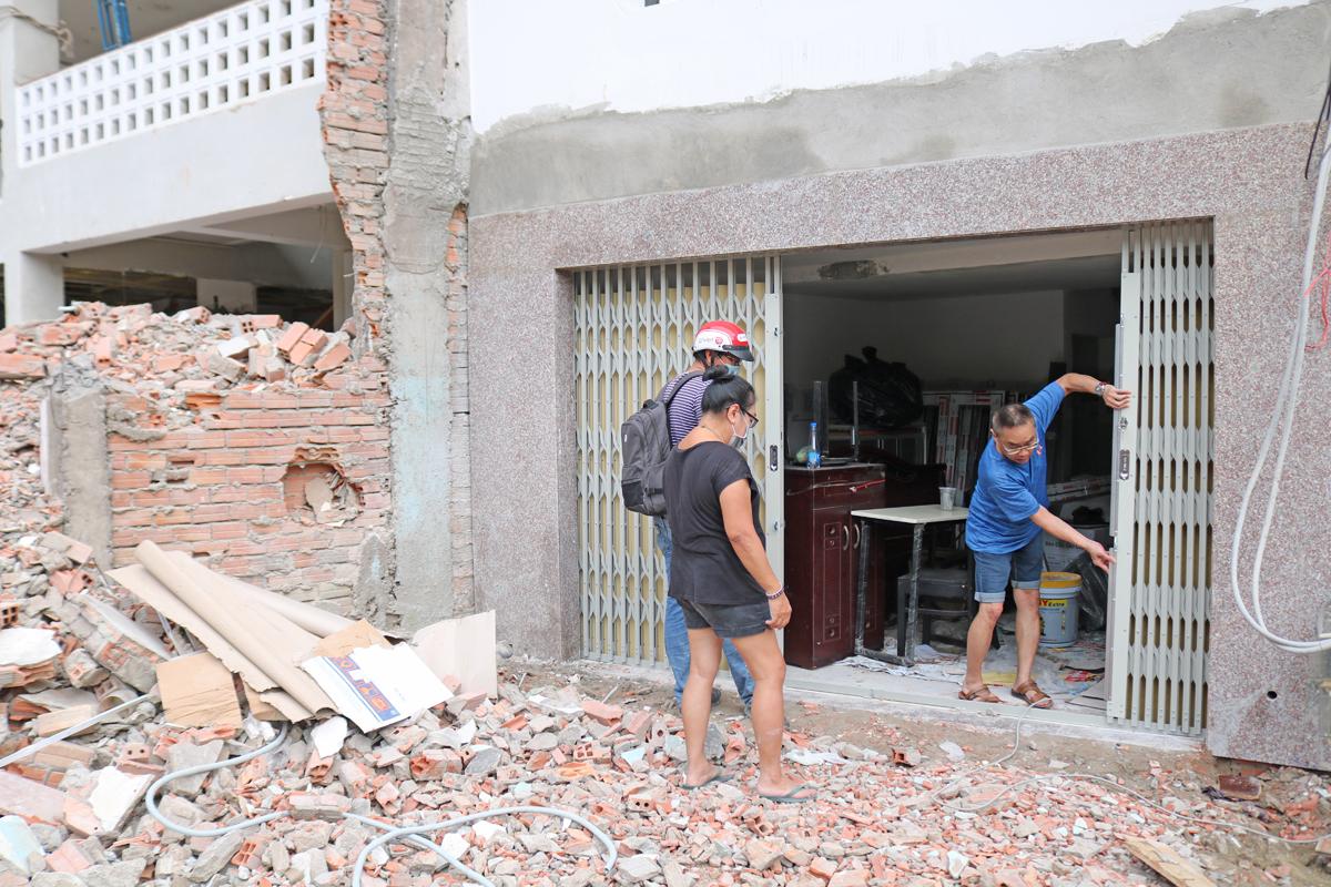 Anh Tuấn Anh (áo xanh) cùng gia đình đang sửa lại nhà sau khi bàn giao lại phần đất phía trước, chiều 27/11. Ảnh: Gia Minh.