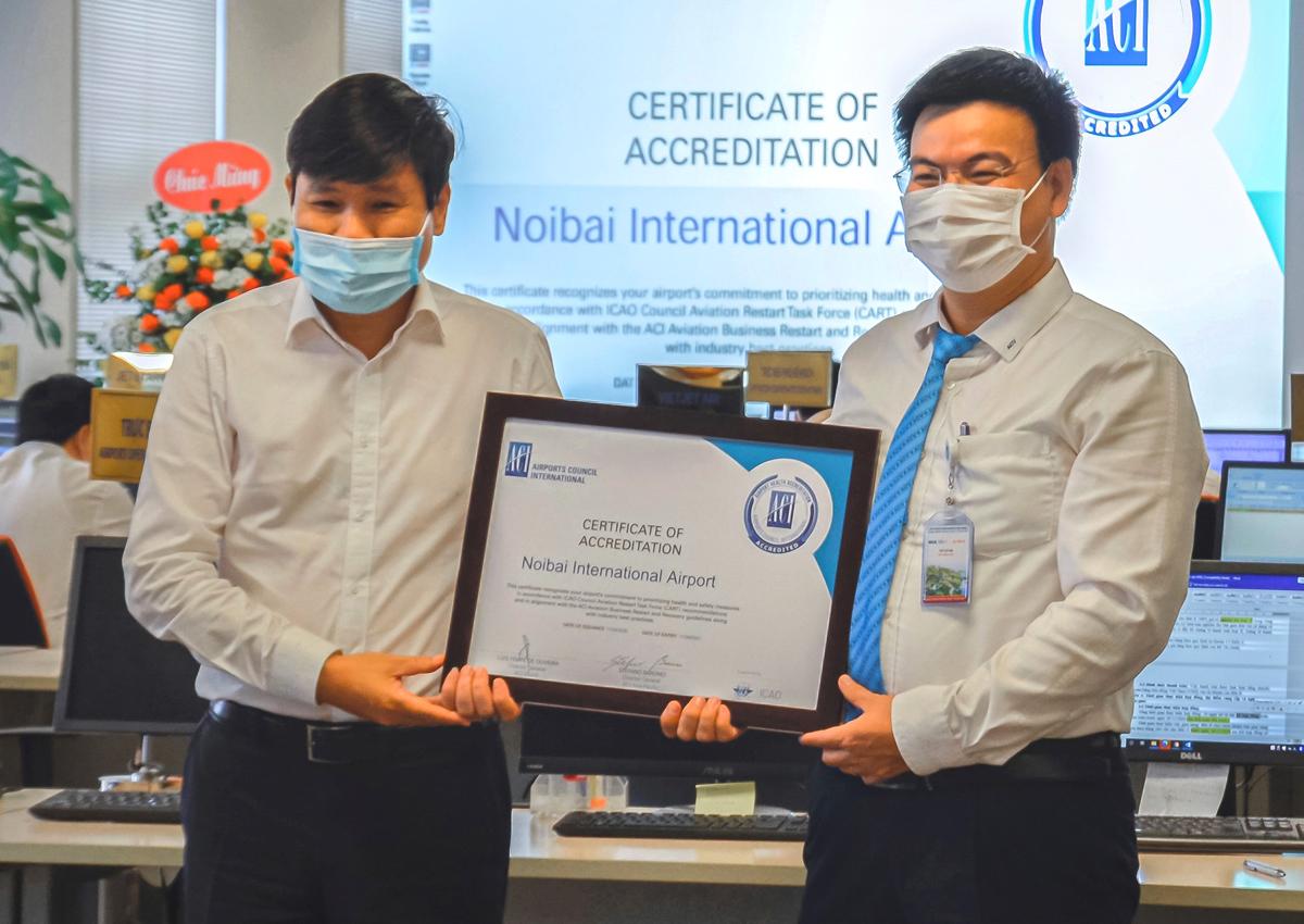 Ông Đinh Việt Thắng, Cục trưởng Hàng không Việt Nam (trái) trao chứng nhận cho lãnh đạo sân bay Nội Bài. Ảnh: NIA.