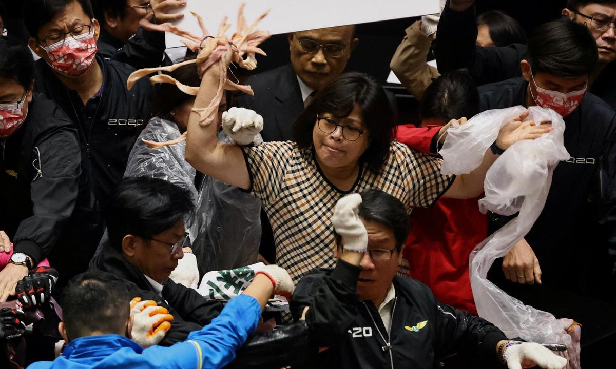 Nghị sĩ ném lòng lợn để phản đối quyết định về nhập khẩu thịt lợn tại nghị viện Đài Loan hôm nay. Ảnh: Reuters.