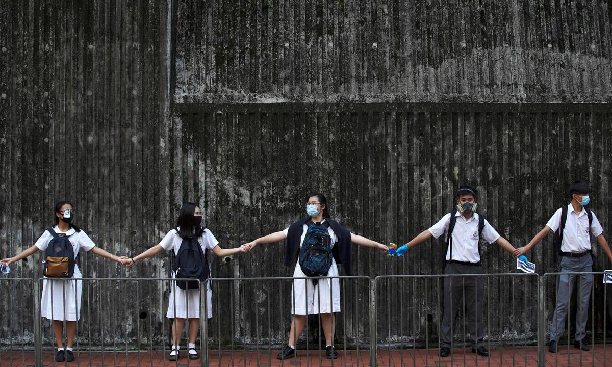 Các học sinh cấp hai nắm tay để kết thành dòng người dài trong cuộc biểu tình ở Hong Kong hồi tháng 9/2019. Ảnh: Reuters.