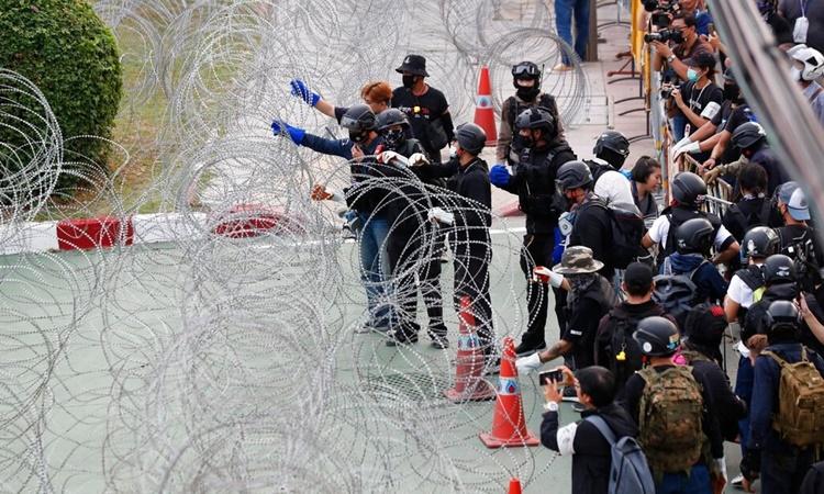 Người biểu tình cố gắng vượt qua hàng rào dây thép gai chắn lối vào doanh trại của Trung đoàn Bộ binh 11 ở thủ đô Bangkok, Thái Lan, ngày 29/11. Ảnh: AP.