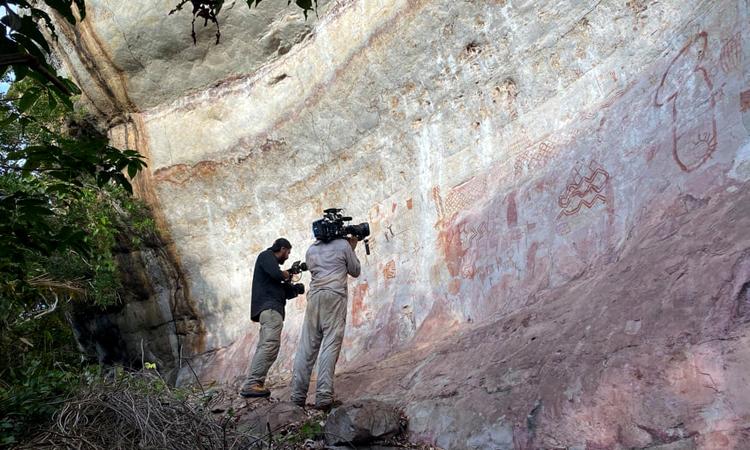 Các nhà làm phim ghi hình vách đá với loạt tranh vẽ cổ xưa. Ảnh: Ella Al-Shamahi.