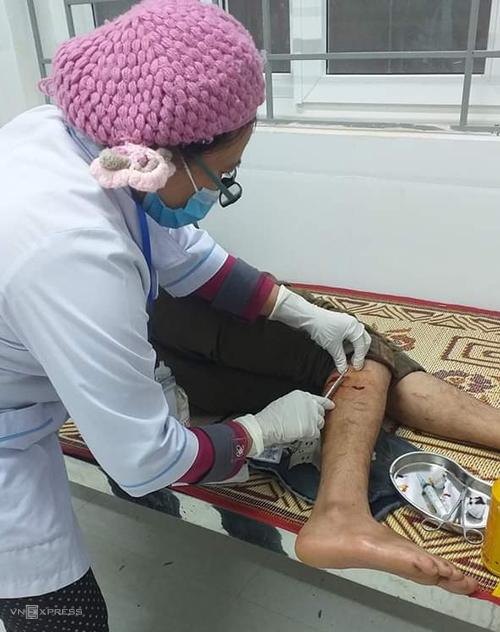 Nhân viên Trạm y tế Hướng Lập sơ cứu cho anh Nguyễn Đình Ngọc, bị voọc cắn vào chiều 29/11. Ảnh: Quang Hà