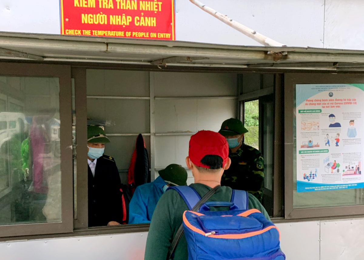 Lưu học sinh Lào làm tờ khai y tế tại chốt kiểm tra thân nhiệt ở cửa khẩu Cầu Treo. Ảnh: Đức Hùng