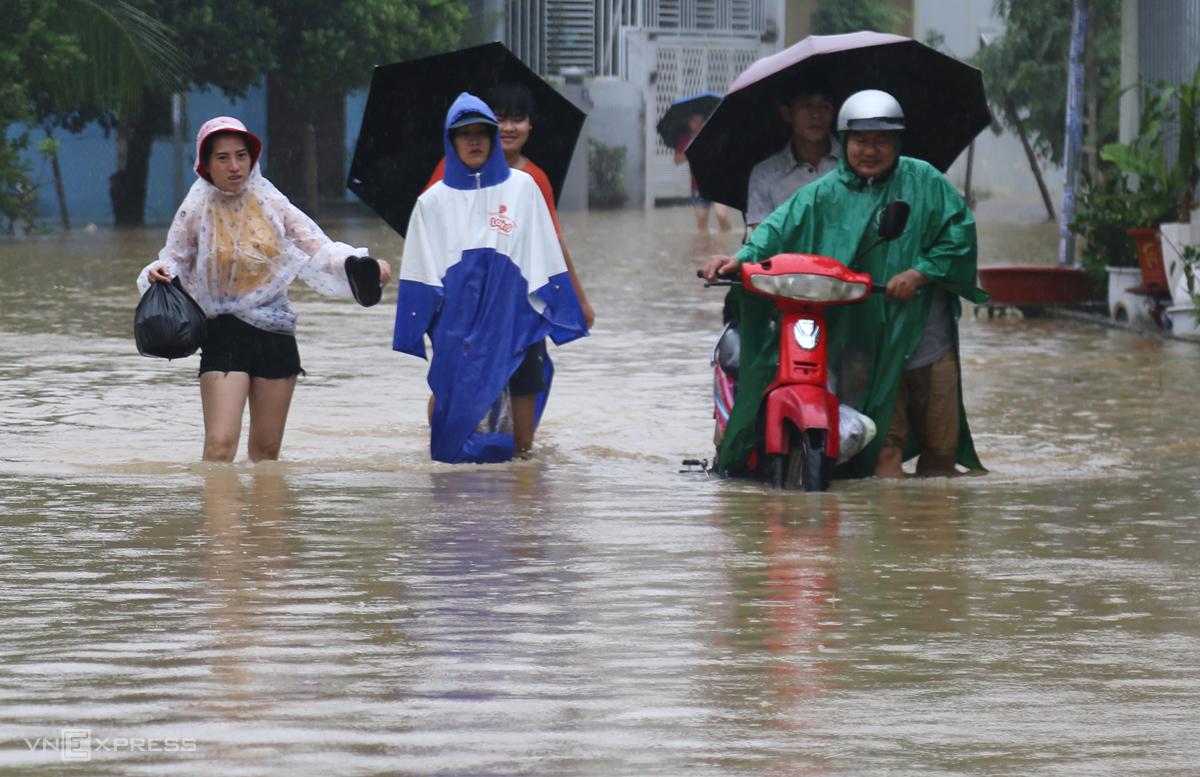 Người dân Nha Trang dắt xe, đi bộ qua khu vực ngập. Ảnh: Xuân Ngọc.