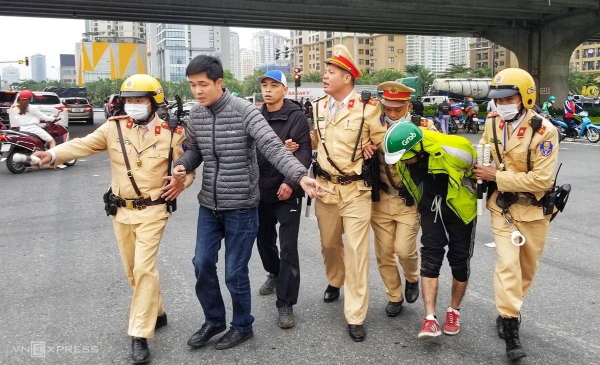 CSGT bắt giữ nghi can cướp điện thoại, dẫn giải về tổ công tác, chiều 1/12. Ảnh: Phạm Tuấn