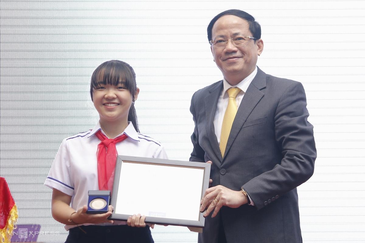 Phương Nhi được Thứ trưởng Thông tin và Truyền thông Phạm Anh Tuấn trao giải ba quốc tế của Liên minh Bưu chính quốc tế  (UPU), sáng 1/12. Ảnh: Thanh Hằng