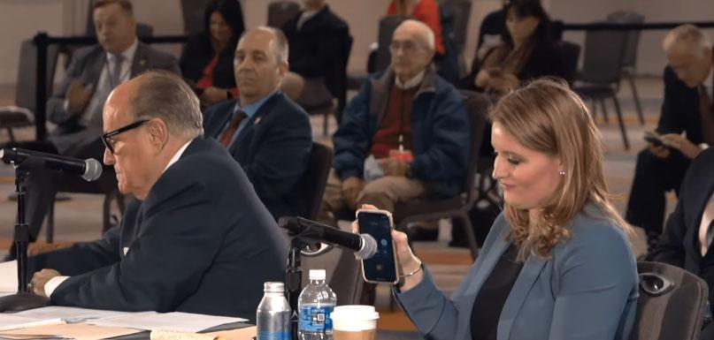 Tổng thống Donald Trump nói qua loa ngoài điện thoại của nữ luật sư Jenna Ellis, cuộc điều trần của các nghị sĩ Cộng hòa tại bang Arizona, hôm 30/11. Ảnh: NTD.