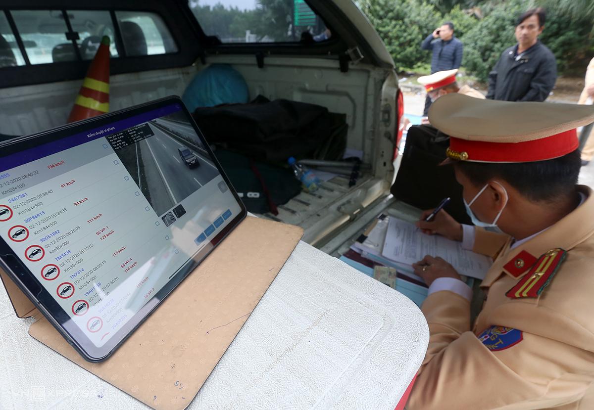 Tổ công tác đội 1 làm nhiệm vụ sáng 2/12 trên cao tốc Nội Bài-Lào Cai được cấp một máy tính bảng kết nối với hệ thống camera, trước khi lập biên bản sẽ cho tài xế xem clip vi phạm. Ảnh: Bá Đô