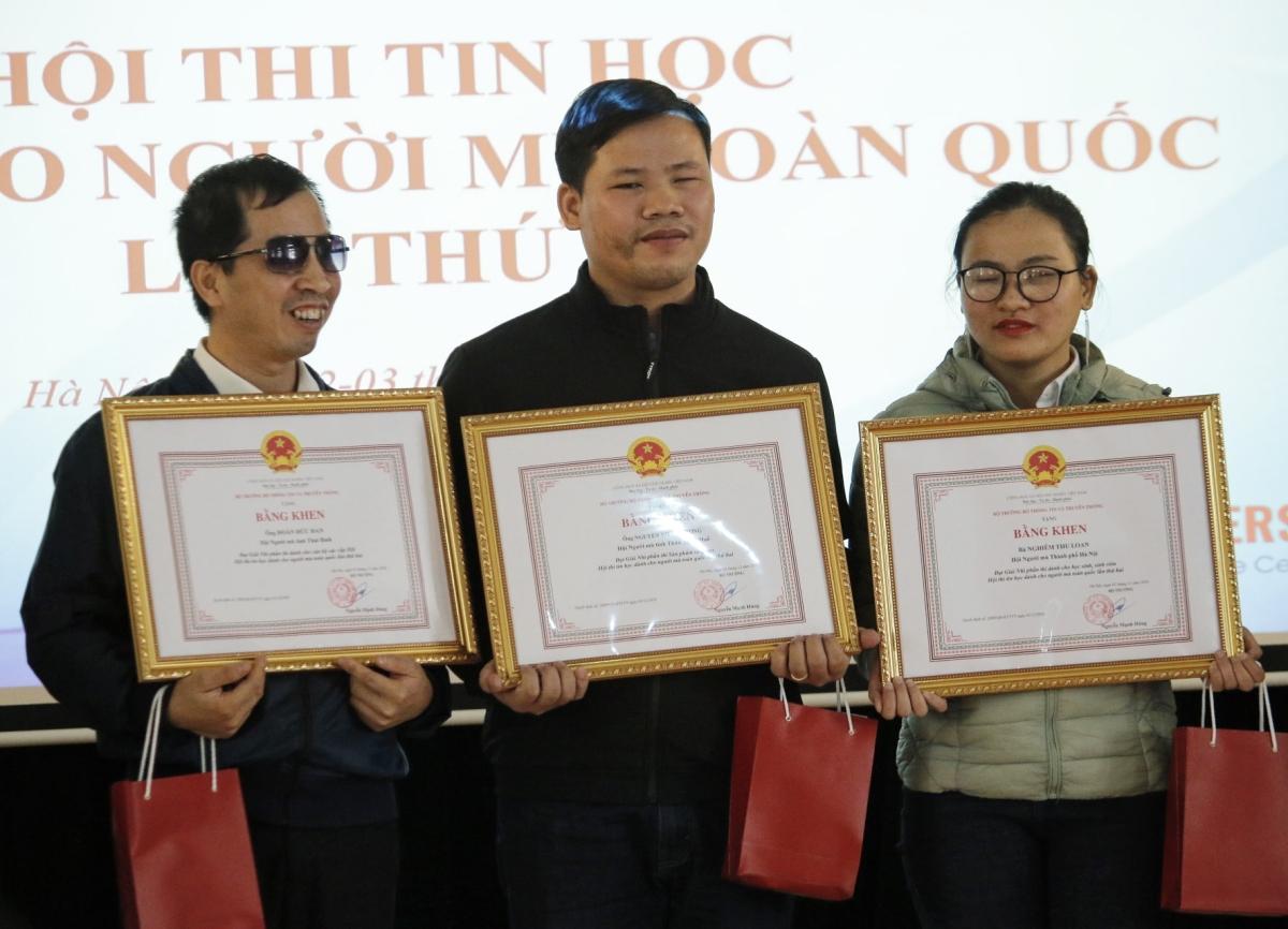 Thí sinh đạt giải nhì Hội thi Tin học dành cho người khiếm thị nhận bằng khen và điện thoại, sáng 3/12. Ảnh: Xuân Hoa