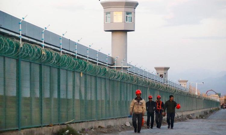 Công nhân đi bộ bên hàng rào được gọi là trung tâm giáo dục kỹ năng nghề ở Dabancheng, Tân Cương, Trung Quốc năm 2018. Ảnh: Reuters.