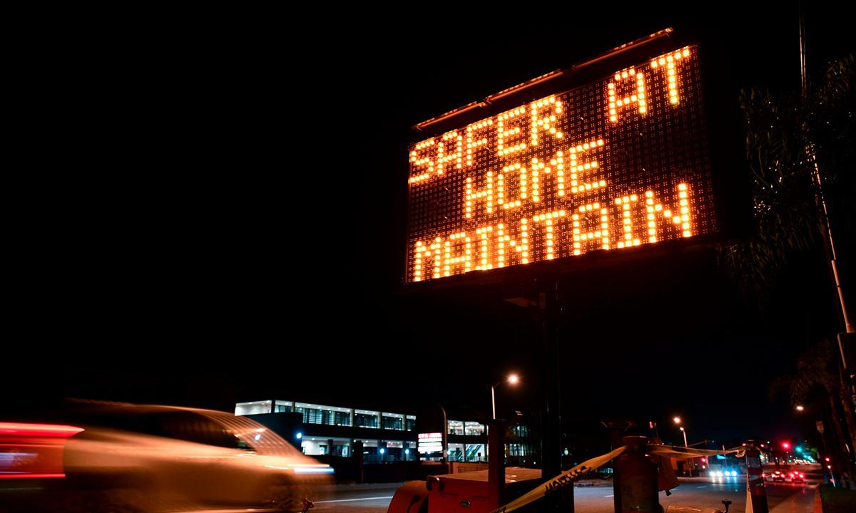 Biển hiệu nhắc nhở người dân thực hiện quy định cách ly tại nhà ở Los Angeles, bang California. Ảnh: AFP.