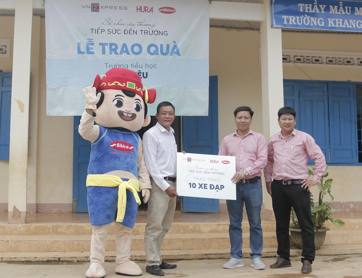 Đại diện nhãn hàng Bibica (phải) trao tặng xe đạp cho thầy Phan Ngọc Tuấn, Hiệu trưởng trường tiểu học Tô Hiệu (trái).