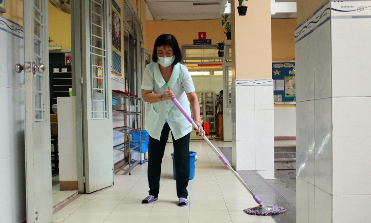 Nhân viên trường Tiểu học Phú Định, quận 6 tổng vệ sinh trường lớp sau mỗi buổi học. Ảnh: Mạnh Tùng.