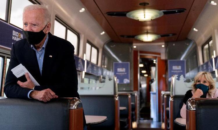 Joe Biden (trái) cùng vợ Jill Biden trên chuyến tàu Amtrak hôm 30/9. Ảnh: AP.