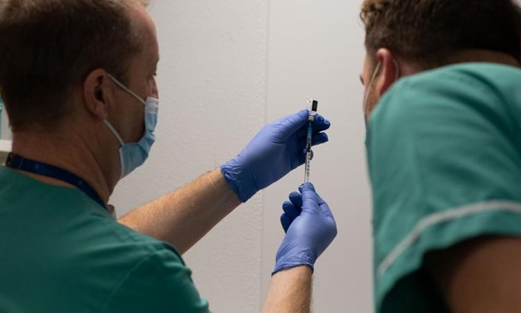 Darrell Baker (trái), giám đốc lâm sàng phụ trách dược phẩm của hội đồng y tế trung tâm tiêm chủng Cardiff, pha một ống tiêm vaccine Covid-19 cùng đồng nghiệp Rhys Oats. Ảnh: CNN.