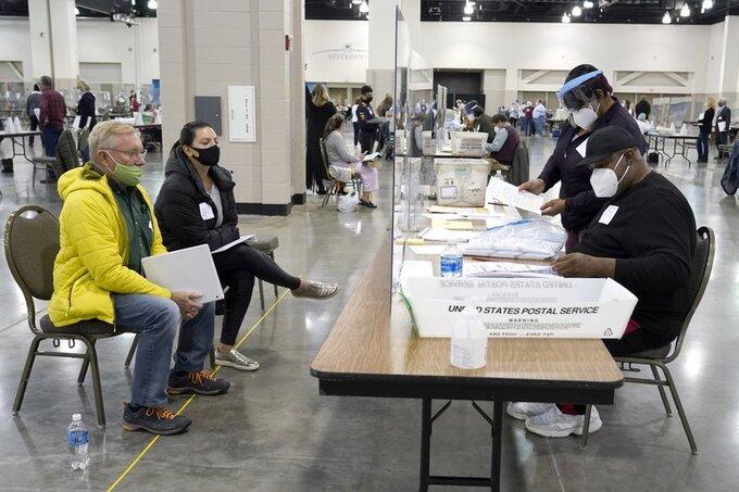 Các nhân viên bầu cử kiểm lại phiếu bằng tay trước sự chứng kiến của hai quan sát viên (trái) tại hạt Milwaukee, bang Wisconsin, hôm 20/11. Ảnh: AP.