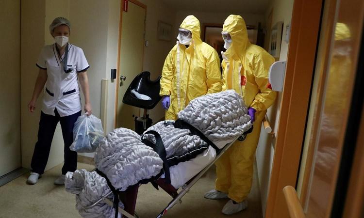 Nhân viên nhà xác chuyển thi thể một bệnh nhân Covid-19 từ một trại dưỡng lão ở Brussels, Bỉ, hồi tháng 4. Ảnh: Reuters.