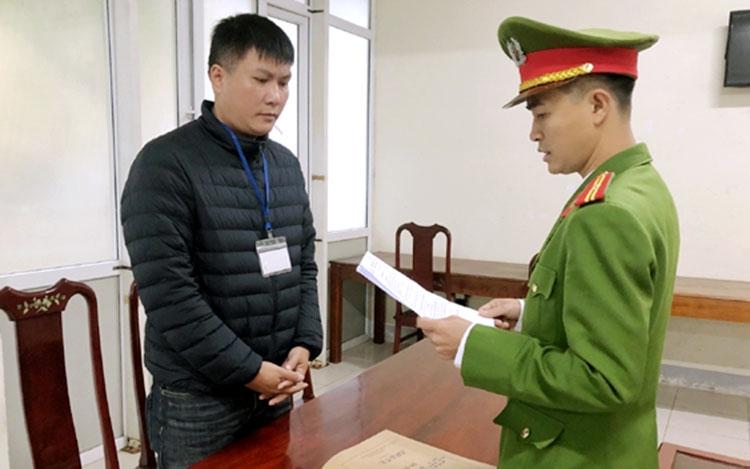 Nghi can Chiến (bên trái) nghe cảnh sát đọc lệnh khởi tố. Ảnh: H.Q