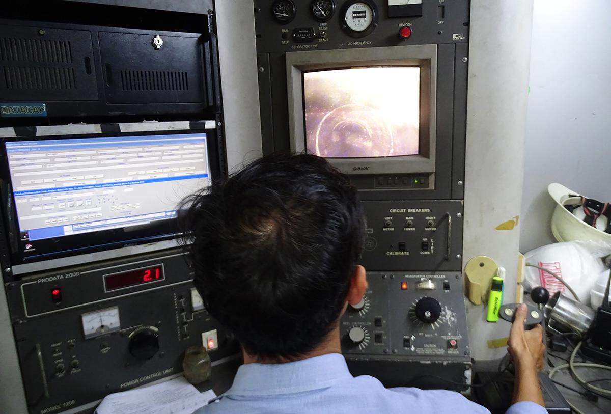Kỹ sư Nguyễn Minh Nhật điều khiển robot kiểm tra cống thoát nước qua màn hình. Ảnh: Hà An.