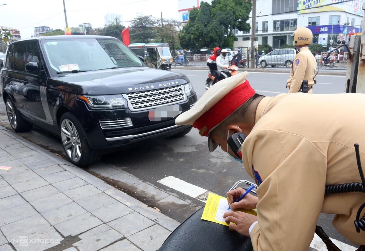Cảnh sát ghi thông báo phạt nguội với xe ôtô vi phạm trên đường Giải Phóng, Hoàng Mai vào sáng 15/12. Ảnh: Phương Sơn