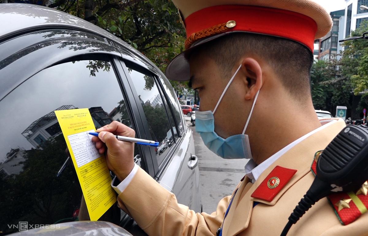 Tổ công tác thuộc Đội CSGT số 6 dán phiếu thông báo phạt nguội trên xe ôtô dừng đỗ trên phố Duy Tân, Cầu Giấy ngày 15/12. Ảnh: Văn Lộc