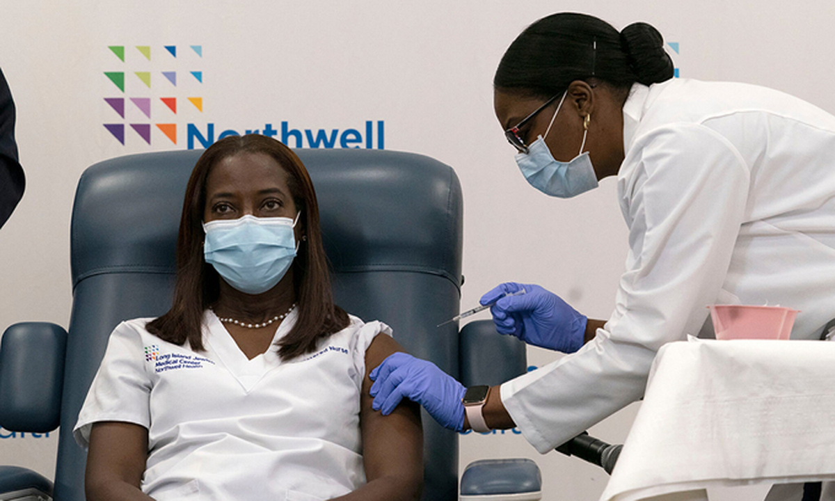 Y tá Sandra Lindsay (trái), người đầu tiên tiêm vaccine Covid-19 ở Mỹ tại Trung tâm Y tế Long Island Jewish hôm 14/12. Ảnh: NYTimes.
