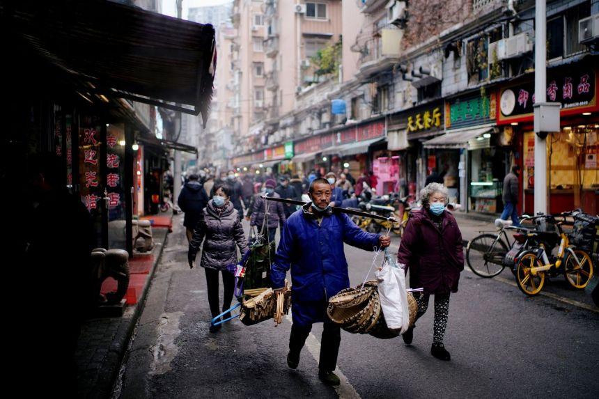 Người dân đi lại tại một khu chợ ở Vũ Hán, Trung Quốc ngày 7/12. Ảnh: Reuters.