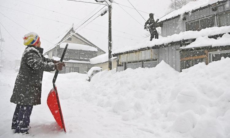 Người dân cố dọn tuyết trên nóc một ngôi nhà ở Minakami, tỉnh Gunma, miền đông Nhật Bản hôm 16/12. Ảnh: Kyodo.