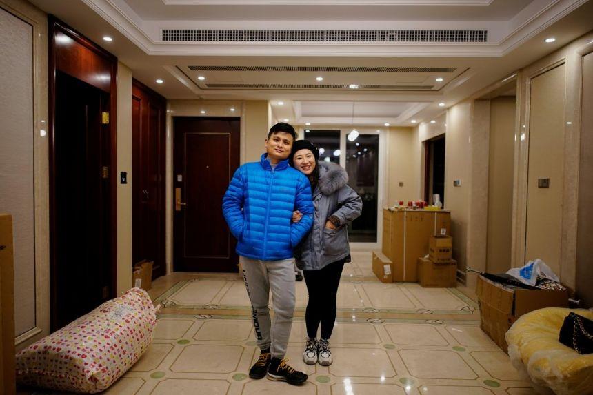 Vợ chồng Duan và Fang trong căn hộ mới ở Vũ Hán hôm 13/12. Ảnh: Reuters
