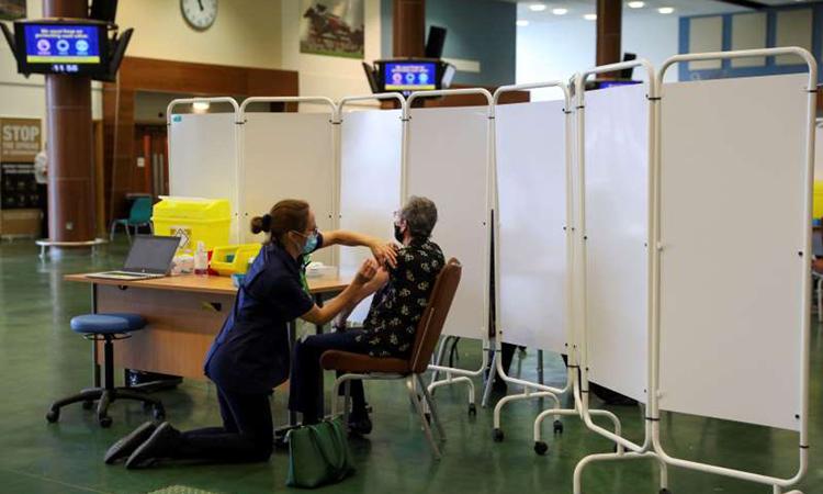 Nhân viên y tế tiêm vaccine Covid-19 tại trung tâm tiêm chủng ở hạt Surrey, Anh hôm 16/12. Ảnh: Reuters.