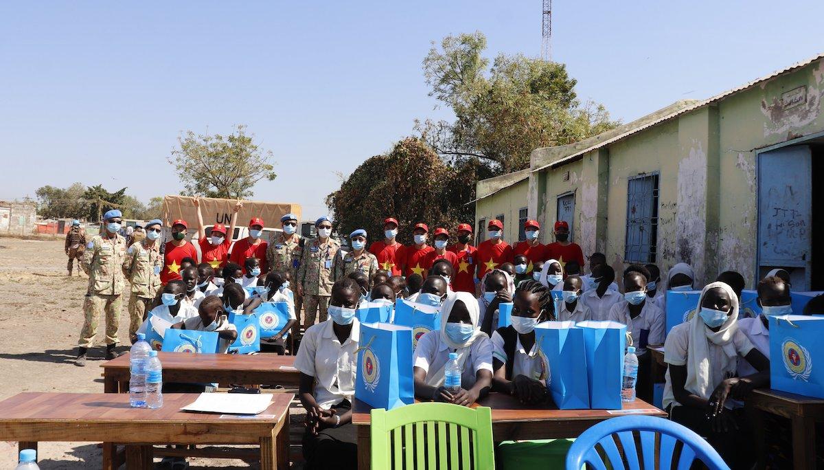 Cán bộ, nhân viên Bệnh viện với các em học sinh, cùng quà tặng và bàn ghế mới. Ảnh: BVDC2.2