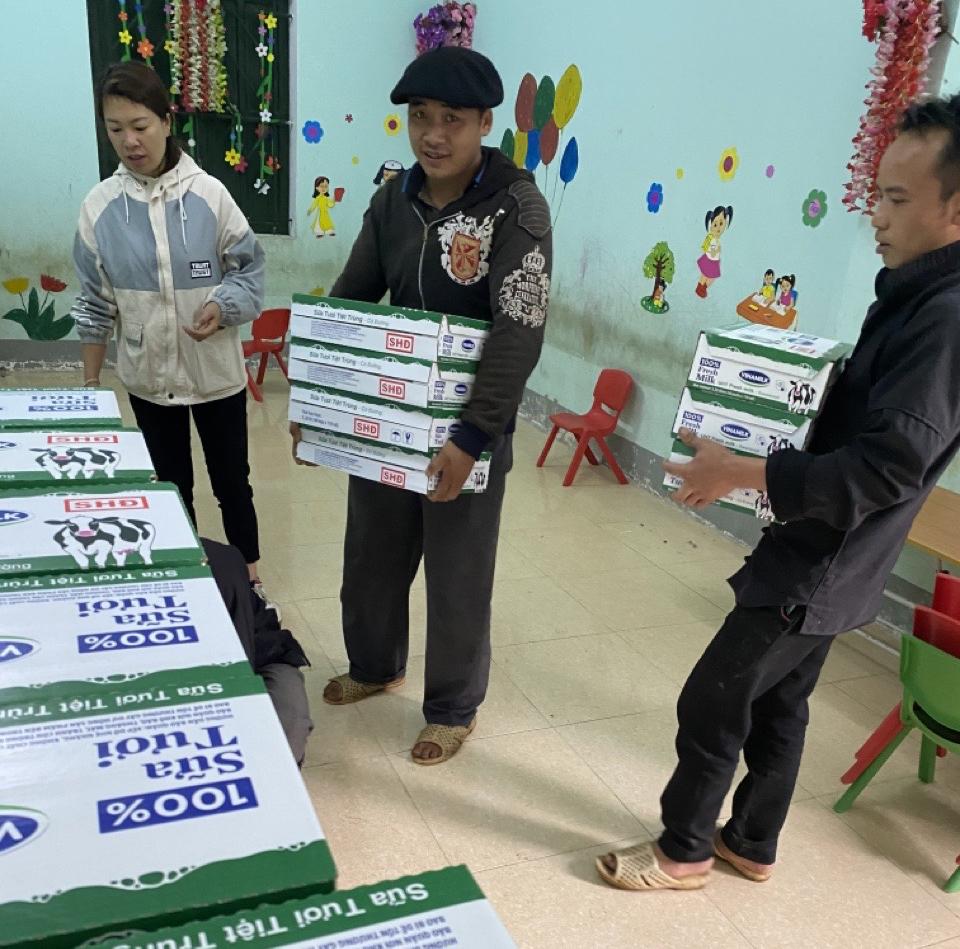 Các thầy cô giáo hỗ trợ các bác tài chuyển sữa vào trường.