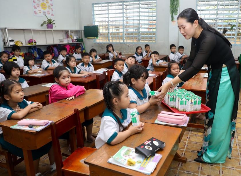 Học sinh tỉnh Vĩnh Long được cô giáo hướng dẫn về dinh dưỡng trong giờ uống Sữa học đường. Ảnh: Quỳnh Trần.