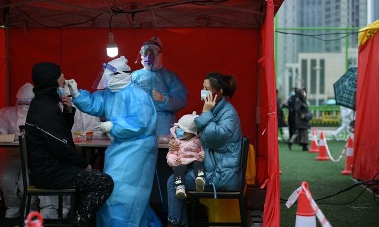 Nhân viên y tế lấy mẫu xét nghiệm Covid-19 cho người dân tại Thiên Tân, Trung Quốc, hồi tháng 11. Ảnh: Reuters.