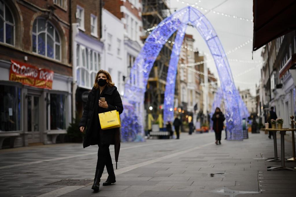 Người đi bộ dọc một đường phố trung tâm London hôm 22/12. Ảnh: AFP.