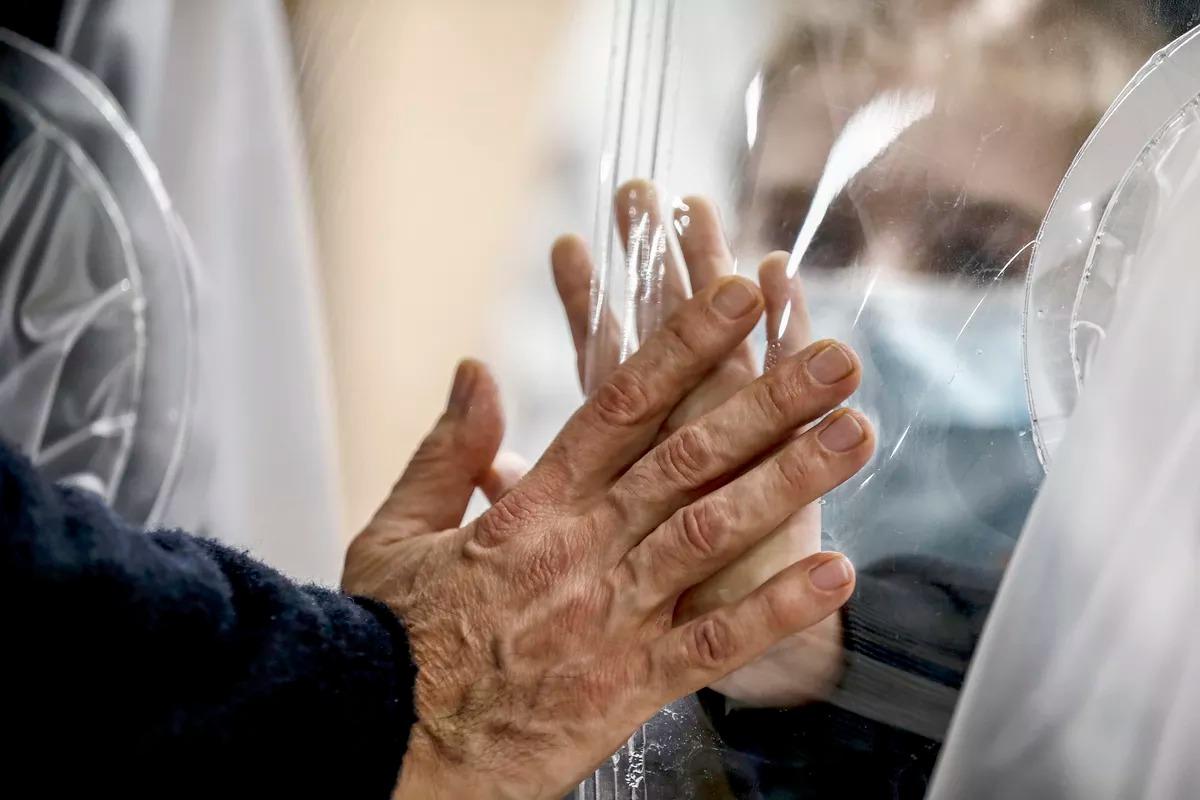 Người thân chạm tay nhau qua màn nhựa để tránh lây nhiễm nCoV tại trung tâm San Raffaele ở Rome ngày 22/12. Ảnh: AP.