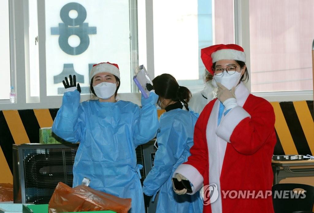 Nhân viên y tế mặc trang phục Noel để khích lệ tinh thần của mọi người tại trung tâm xét nghiệm Covid-19 ở thành phố Gwangju, Hàn Quốc, hôm 24/12. Ảnh: Yonhap.
