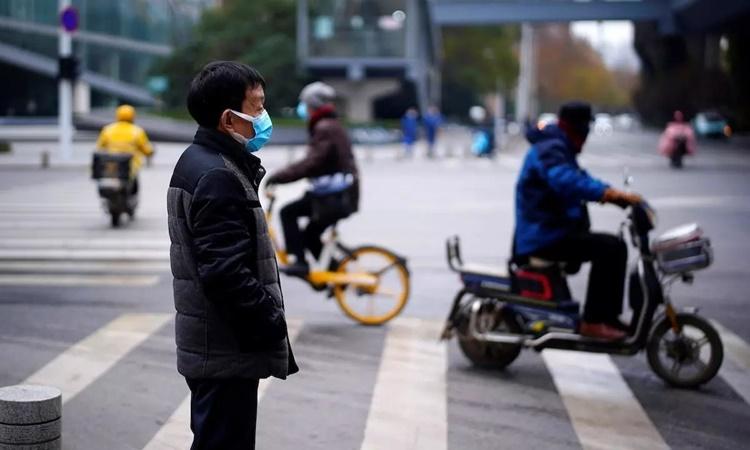Người dân đi lại trên đường phố Vũ Hán hôm 17/12. Ảnh: AFP.