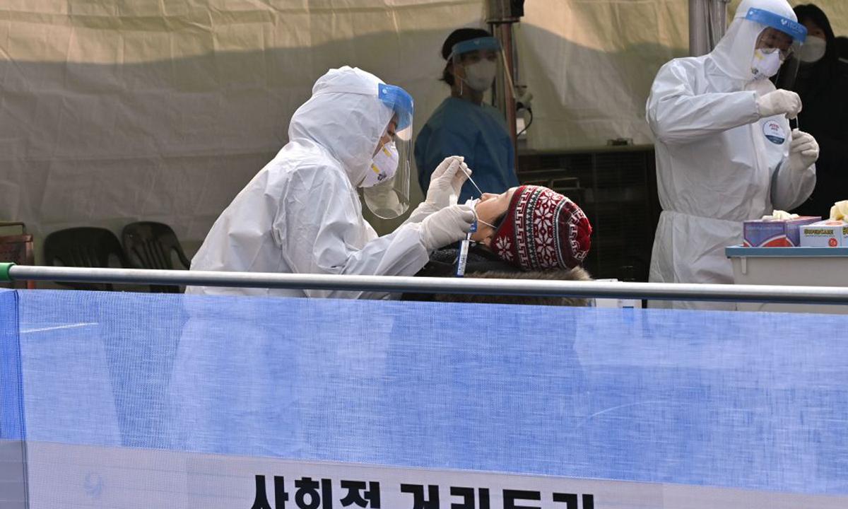 Nhân viên y tế lấy mẫu xét nghiệm nCoV cho người dân tại ga tàu điện Seoul, Hàn Quốc hôm 22/12. Ảnh: AFP.