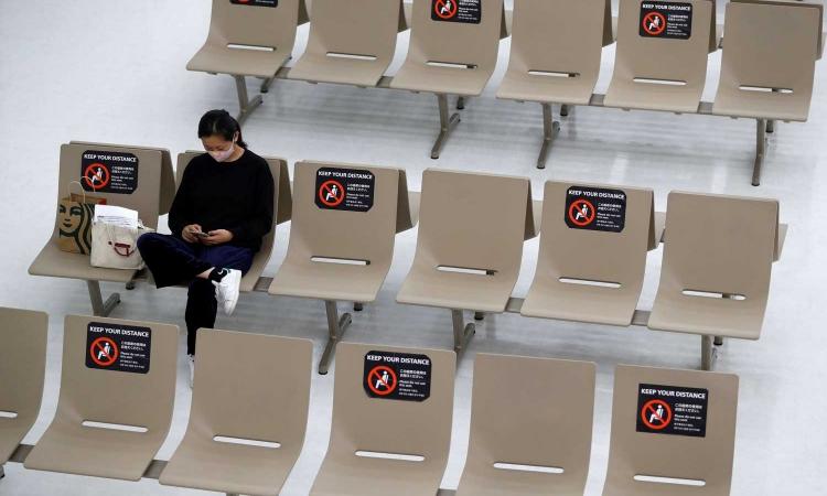 Một phu nữ ngồi chờ ở sân bay quốc tế Narita, Nhật Bản, hôm 2/11. Ảnh: Reuters.