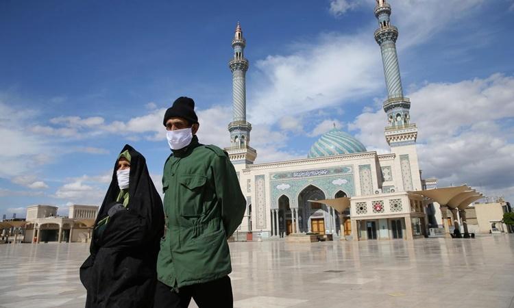 Người dân đeo khẩu trang trên đường phố thành phố Qom, Iran, hồi tháng ba. Ảnh: Reuters.